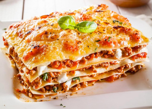 Portion of traditional durum wheat lasagne with bolognaise sauce, beef mince and cheese in alternating layers on a white plate